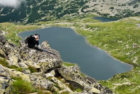 spunk: Hiker girl in Retezat mountain,siting on a rock above Bucura lake Stock Photo