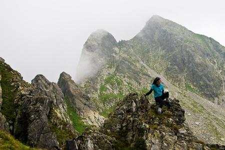 Hiker girl in Retezat mountain,siting on a rock photo