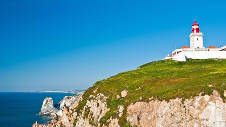 Cabo da Roca (Cape Roca) is a cape which forms the westernmost point of both mainland Portugal and mainland Europe. The cape is in the Portuguese municipality of Sintra, west of Lisbon district, and also forms the westernmost extent of the Serra de Sintra Stock Photo