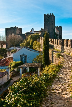 fortified wall: A view of the fortified wall in Obidos, Portugal. The name Obidos probably derives from the Latin term oppidum, meaning citadel, or fortified city Stock Photo