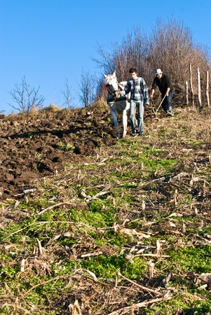 Two farmers ploughing the land the old traditional way with horse and plough photo