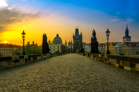 Charles bridge with its statuette and the roofs of the building from Old Town, in Prague during the sunrise, Bohemia, Czech Republic photo