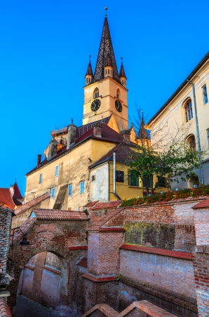 Evanghelical Church s famous tower, landmark of Sibiu, with a medieval street and some of the old town fortification walls photo
