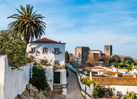derives: A view of the fortified wall in Obidos, Portugal  The name Obidos probably derives from the Latin term oppidum, meaning citadel, or fortified city Stock Photo