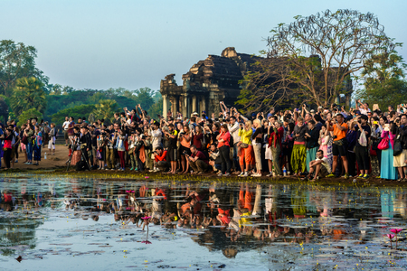 january sunrise: Siem Reap, Cambodia - January 05, 2014  Sunrise at Angkor Wat in Cambodia - a crowd of tourists gathers to watch and photograph the sunrise