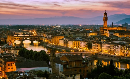 Florence, Italy - skyline view over Arno river with Ponte Vecchio and Palazzo Vecchio at sunset