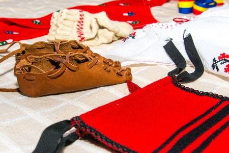 Traditional costume from Romania with peasant s sandal from a baby baptize