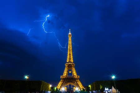 champs elysees quarter: Paris, France - June 8th, 2014  Thunderstorms behind Eiffel Tower illuminated at night-during Roland Garros tour  The Eiffel Tower was built in 1889, and is a popular attraction for tourists