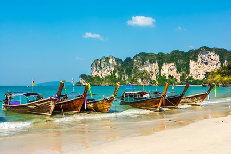 Longtail boats on Railey beach, Krabi, Thailand  Beautiful scenery with blue water and limestone cliffs photo