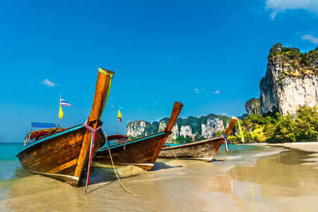 Longtail boats on Railey beach, Krabi, Thailand  Beautiful scenery with blue water and limestone cliffs Stock Photo
