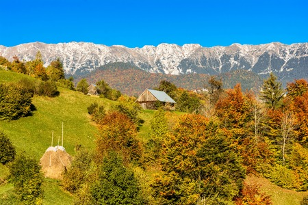 Countryside landscape in a romanian villlage at the food of Piatra Craiului Mountains. Stock Photo