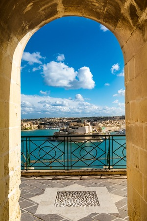 Night view of a harbor in Valletta, Malta view from an arcade frame Stock Photo