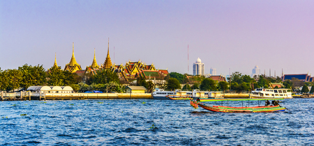 Sunset view across the Grand Palace, with the Chao Praya River and colorful boats in the foreground, Bangkok,Thailand