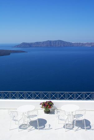Stunning outdoor seating at the terrace over the caldera on vibrant blue Aegean sea, Santorini island Stock Photo
