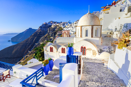 Fira, Santorini - Greek Islands landmark with white village, cobbled paths, greek orthodox blue church and sunset over caldera. Cyclades, Greece Stock Photo