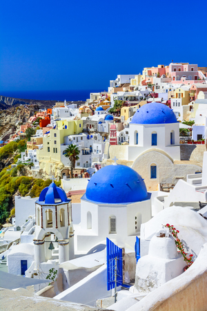 Oia town, Santorini island, Greece at sunset. Traditional and famous white houses and churches  with blue domes over the Caldera, Aegean sea. Фото со стока