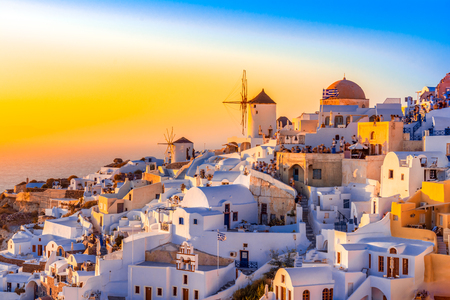 Sunset in Oia town, Santorini island, Greece. Traditional and famous white houses and churches  with blue domes over the Caldera, Aegean sea. Reklamní fotografie