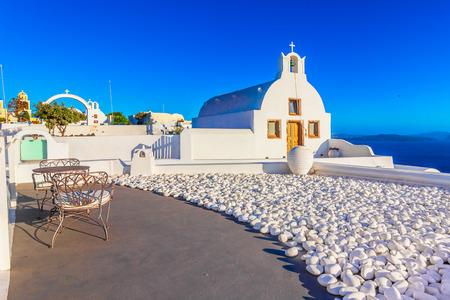 Oia town, Santorini island, Greece at sunset. Traditional and famous white churches  over the Caldera, Aegean sea.