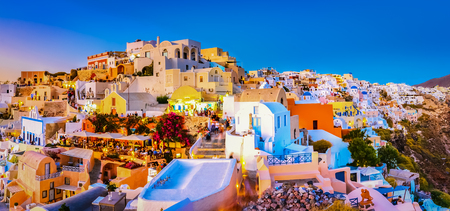 Panoramic view of Oia town, Santorini island, Greece at sunset. Traditional and famous white houses and churches  with blue domes over the Caldera, Aegean sea. Reklamní fotografie
