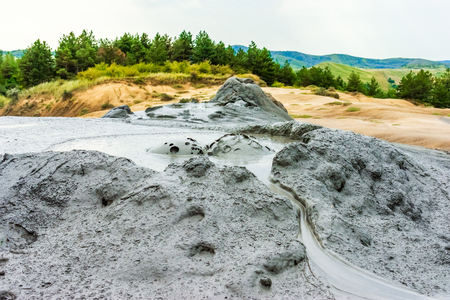 Buzau, Paclele mari, Romania: Bubbling mud, landscape with muddy volcano at sunset - landmark attraction
