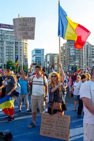 Bucharest, Romania - 10 August 2018: A young couple showing banners at the Diaspora protest against the way Romania is governed by Social Democrats Redakční