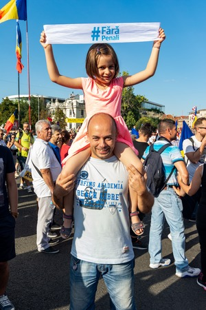 Bucharest, Romania - 10 August 2018: Father and daughter with other tens of thousands of protesters have rallied in cities across Romania against the way Romania is governed by the ruling Social Democrat-PSD