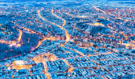Brasov, Romania. Aerial view of the medieval city covered in snow with main square-Christmas market, Xmas Tree and old houses rooftops in Transylvania, Eastern Europe.