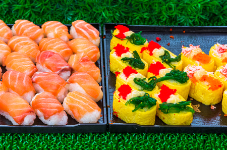 Sushi rolls japanese delicacy. Japanese traditional food from rice and fish or sea food.  A set of delicious delicacies in a day market in Thailand, Asia Фото со стока