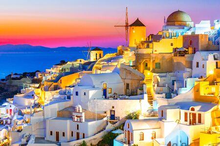 Sonnenuntergang in Oia, Santorini-Insel, Griechenland bei Sonnenuntergang. Traditionelle und berühmte weiße Häuser und Kirchen mit blauen Kuppeln über der Caldera, Ägäis.
