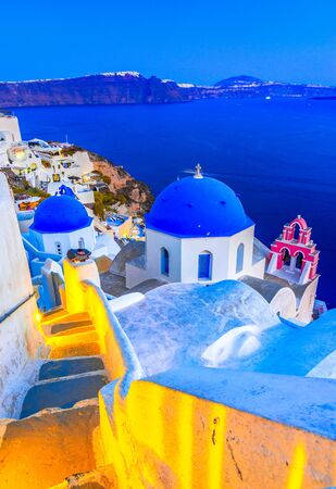 Oia town, Santorini island, Greece at sunset. Traditional and famous white houses and churches  with blue domes over the Caldera, Aegean sea. Reklamní fotografie