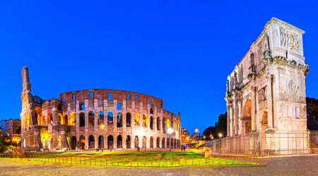Rome, Italy: Night view of The Arch of Constantine next to the Colosseum after sunset over a blue sky. Colosseum is an elliptical amphitheatre or the Flavian Amphitheatre Reklamní fotografie