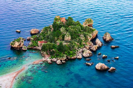 Taormina, Sicily, Italy: Beautiful landscape and seascape with beach and island Isola Bella at sunset, aerial view