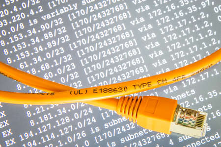 Orange internet cable on gray background with ip addresses Foto de archivo