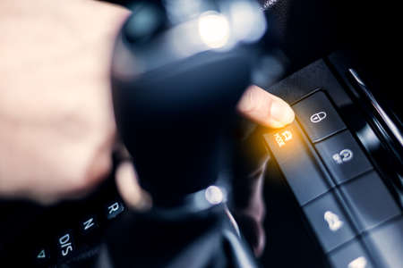 Selecting drive mode in the car. Man's hand touch the button on control panel