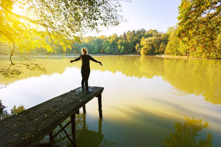 Woman open arms on the pier of the pond. Autumn landscape on a sunny day