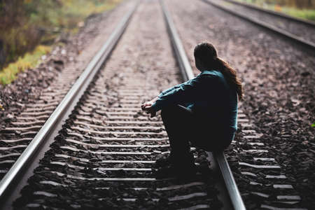 Young man sitting on the railway track and thinking about life