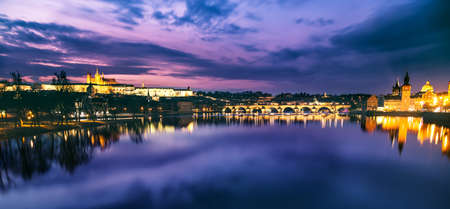Prague evening panorama. Prague Castle with Carles Bridge reflect in Vltava river during sunset