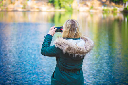 Rear view on blonde woman who taking photo with smartphone. Taking picture of nature by mobile phone