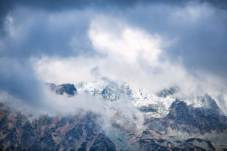 Tatra mountain peaks in clouds. Snowy mountains and fog.