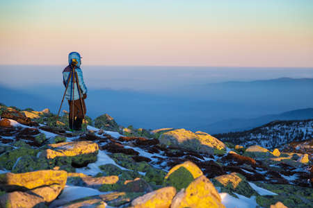 Photographer in the mountans. Mountain peak with stones during evening sun. Inversion weather in bacground Zdjęcie Seryjne