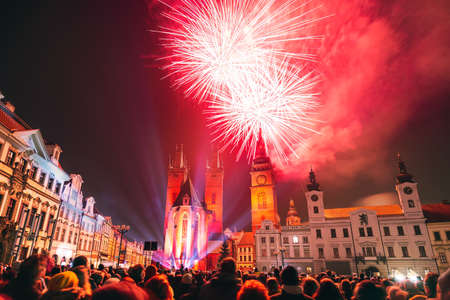 Red fireworks in historic city center of Hradec Kralove, Czech Republic. Crowd of people in foreground.