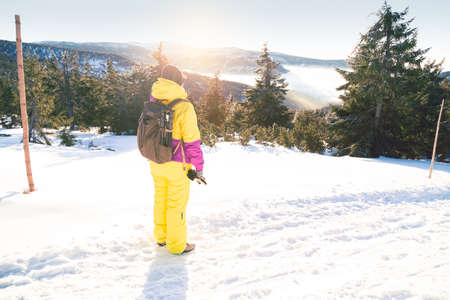 Tourist in Krkonose mountains. Girl in yellow winter clothes on winter tour over the mountain ridges. View to valley with fog. View of valley with fog. Zdjęcie Seryjne