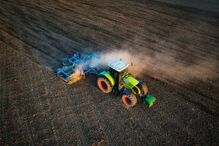 Aerial drone view of tractor plowing on the field during evening sunlight Zdjęcie Seryjne