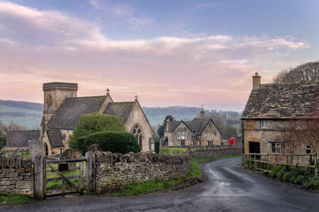 Snowshill church in the Cotswolds gloucestershire with lane leading past a cottage towards red telephone box and country pub Banco de Imagens