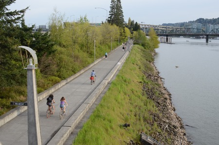 eastbank: People biking and jogging along the Eastbank  in Portland, Oregon. Marquam and Hawthorne bridges in background.