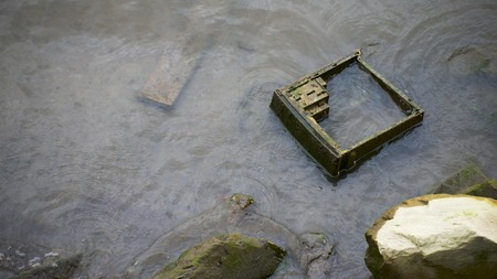 Discarded computer case on a riverbank covered in grime and algae.