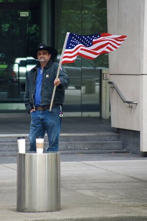 PORTLAND, OREGON JUNE 15 2016 Man in front of a federal courthouse waving a US flag protesting the court case against participants of the armed occupation of the Malheur National Wildlife Refuge.