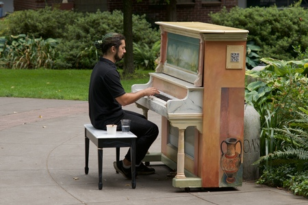 PORTLAND, OREGON AUGUST 3 2016, man playing a piano installed in a public park. The decorated piano installed by the PIANO. PUSH. PLAY. organization.