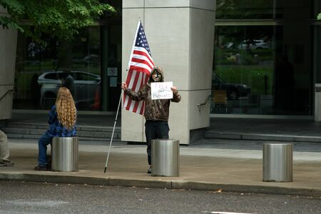 PORTLAND, OREGON SEPTEMBER 7 2016, Masked protester of the trial of the armed occupation of the Malheur National Wildlife Refuge, in front of a federal courthouse holding a sign and American flag. Editorial