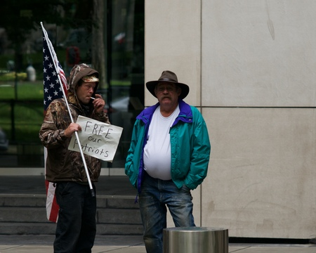 standoff: PORTLAND, OREGON SEPTEMBER 7 2016, Protester of the trial of the armed occupation of the Malheur National Wildlife Refuge, in front of a federal courthouse, smoking, holding a sign and American flag. Editorial